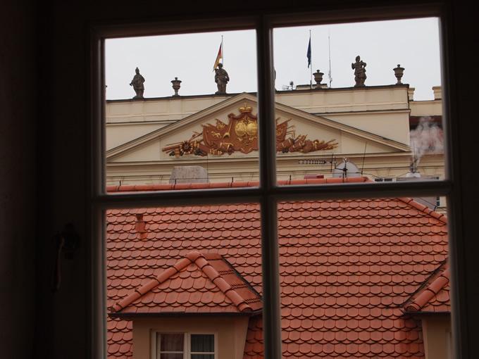 窓から見えるとなりの建物の上に銅像が